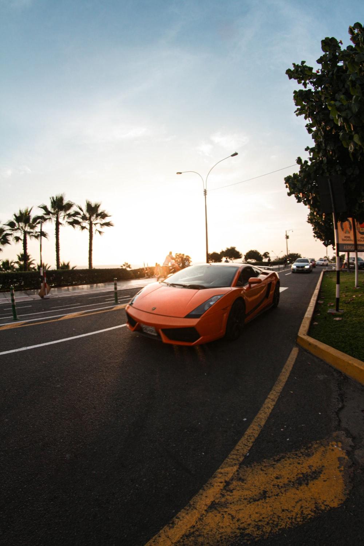 orange sports car on road during daytime