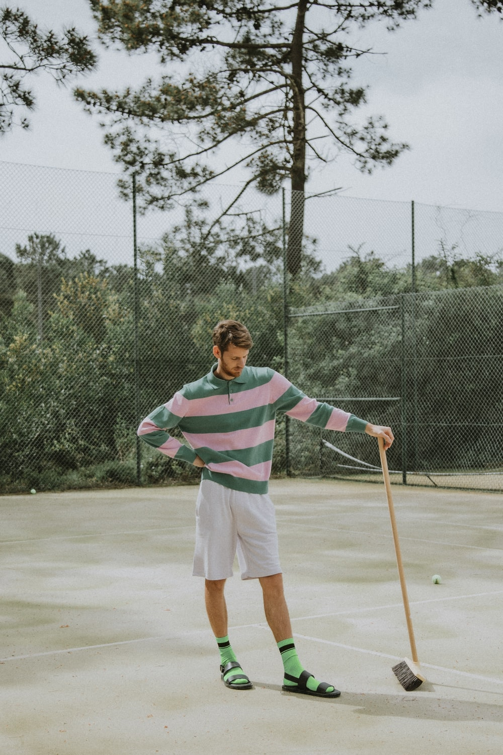 man in red and white stripe polo shirt and white shorts holding brown wooden stick