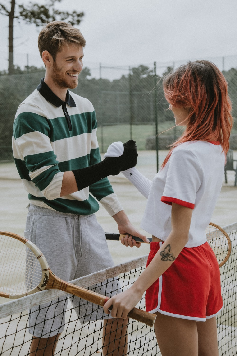 man in white and green striped polo shirt holding brown tennis racket