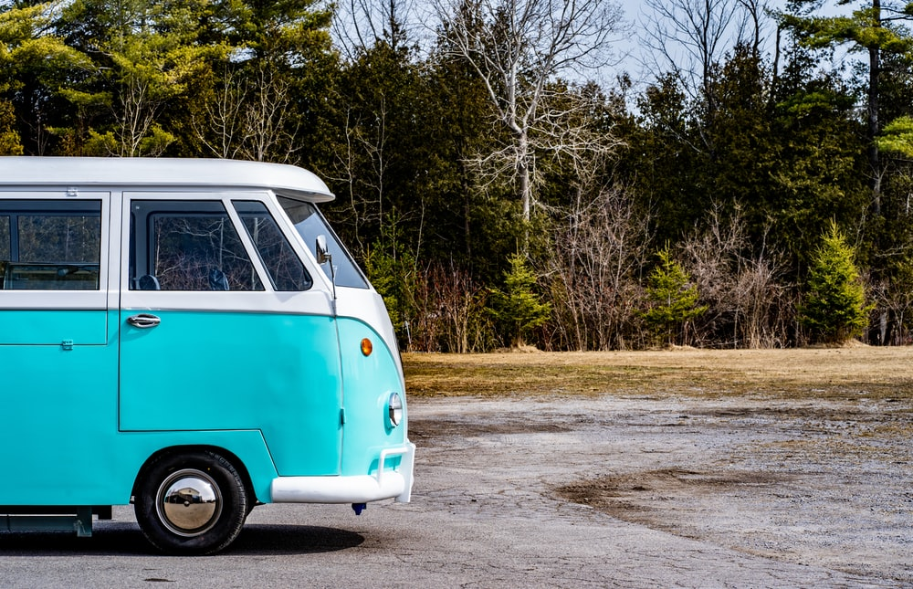 blue and white volkswagen t-2 parked on the side of the road