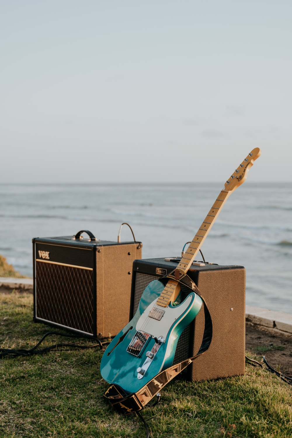brown and black guitar amplifier on brown wooden dock during daytime