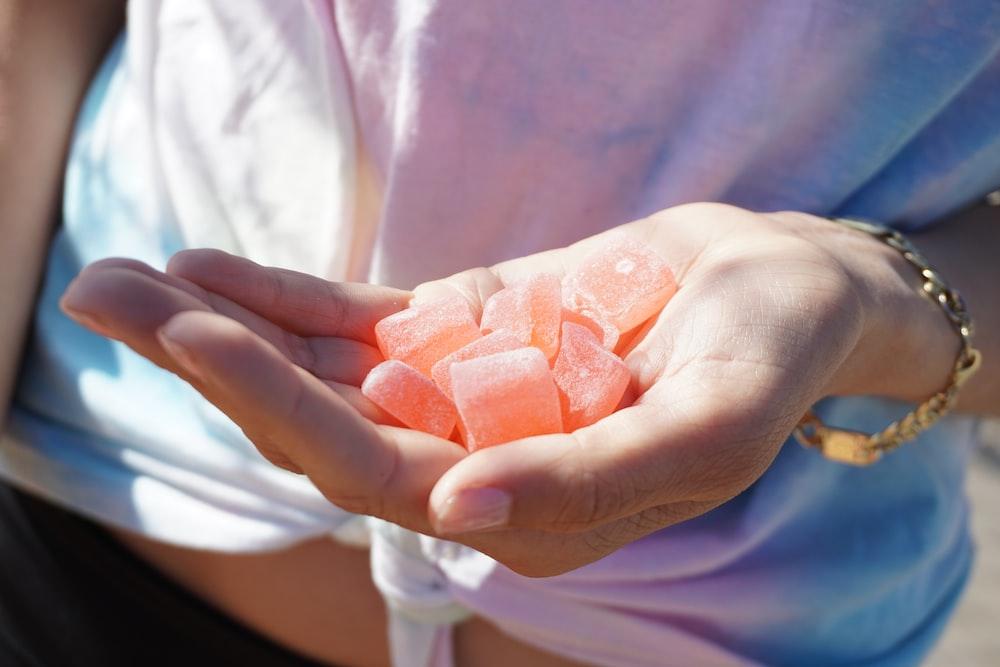 person holding orange medicine tablets