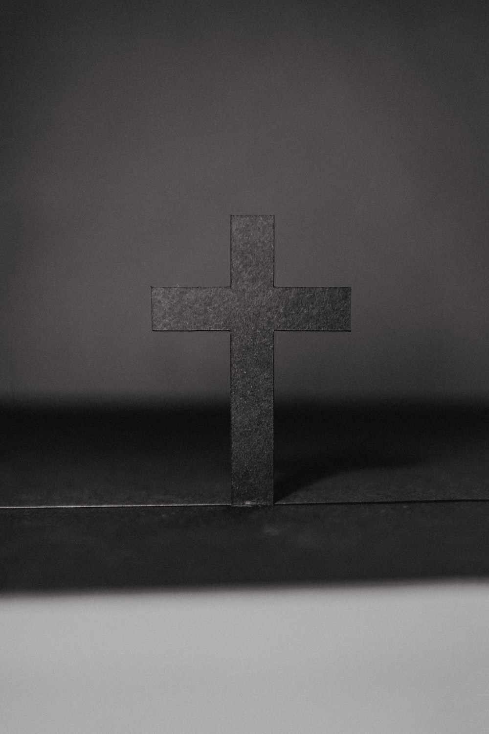 grayscale photo of cross on table