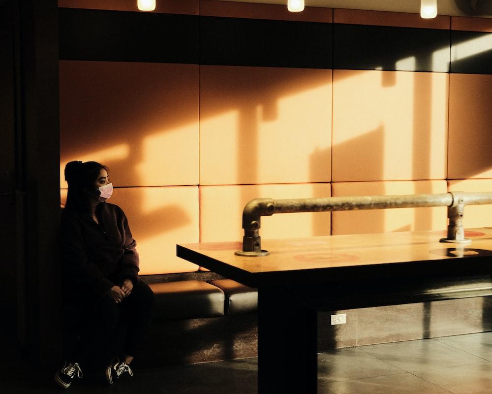 man in black jacket sitting on brown wooden bench