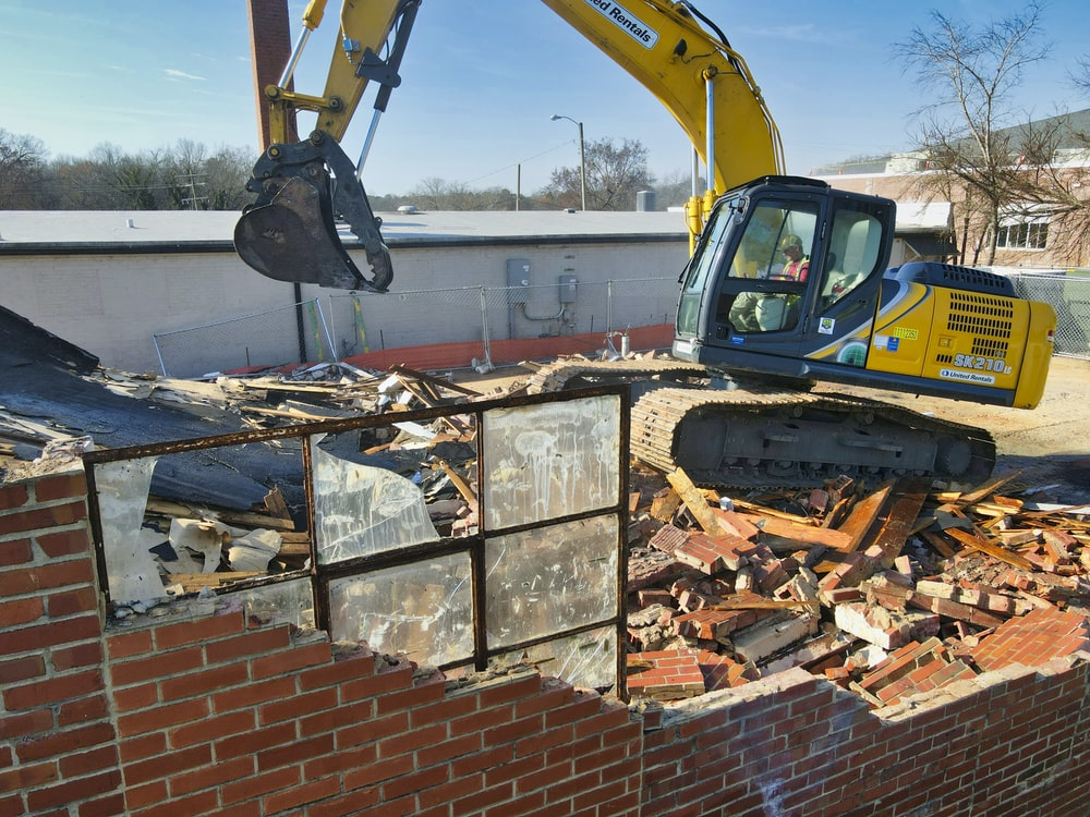 yellow and black excavator on brown brick wall during daytime