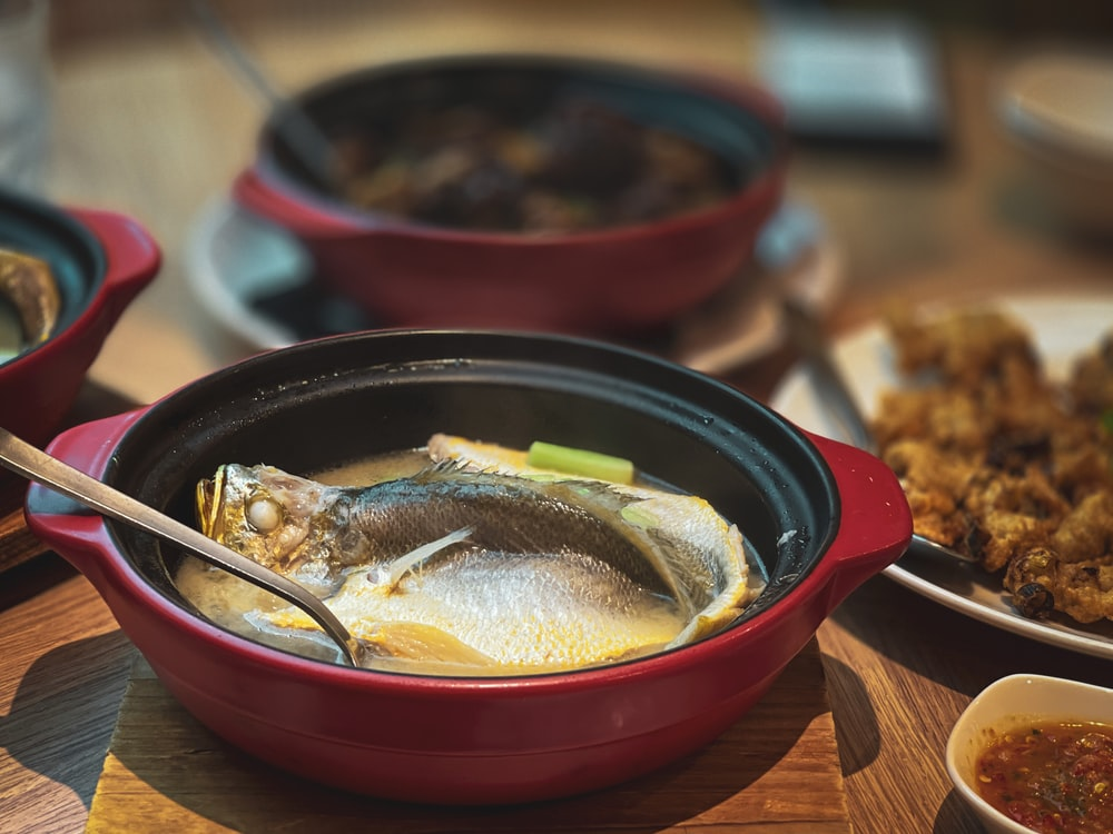 black and red ceramic bowl with food on brown wooden table
