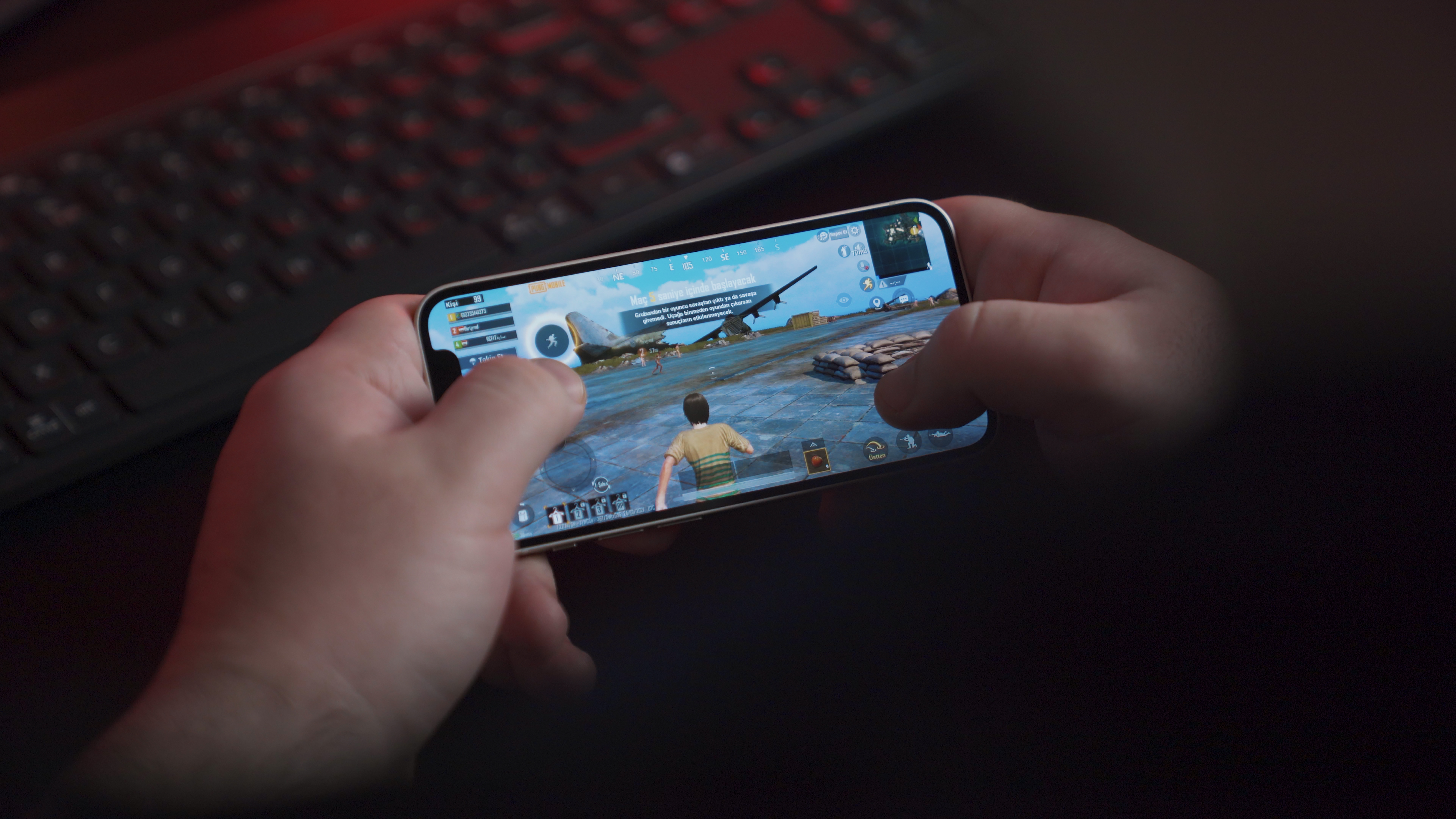 Young man playing PUBG Mobile with iPhone