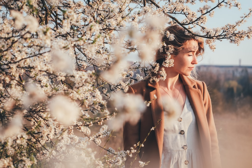 woman in brown coat standing under white cherry blossom tree during daytime