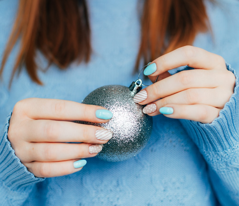 woman in blue long sleeve shirt holding silver ball