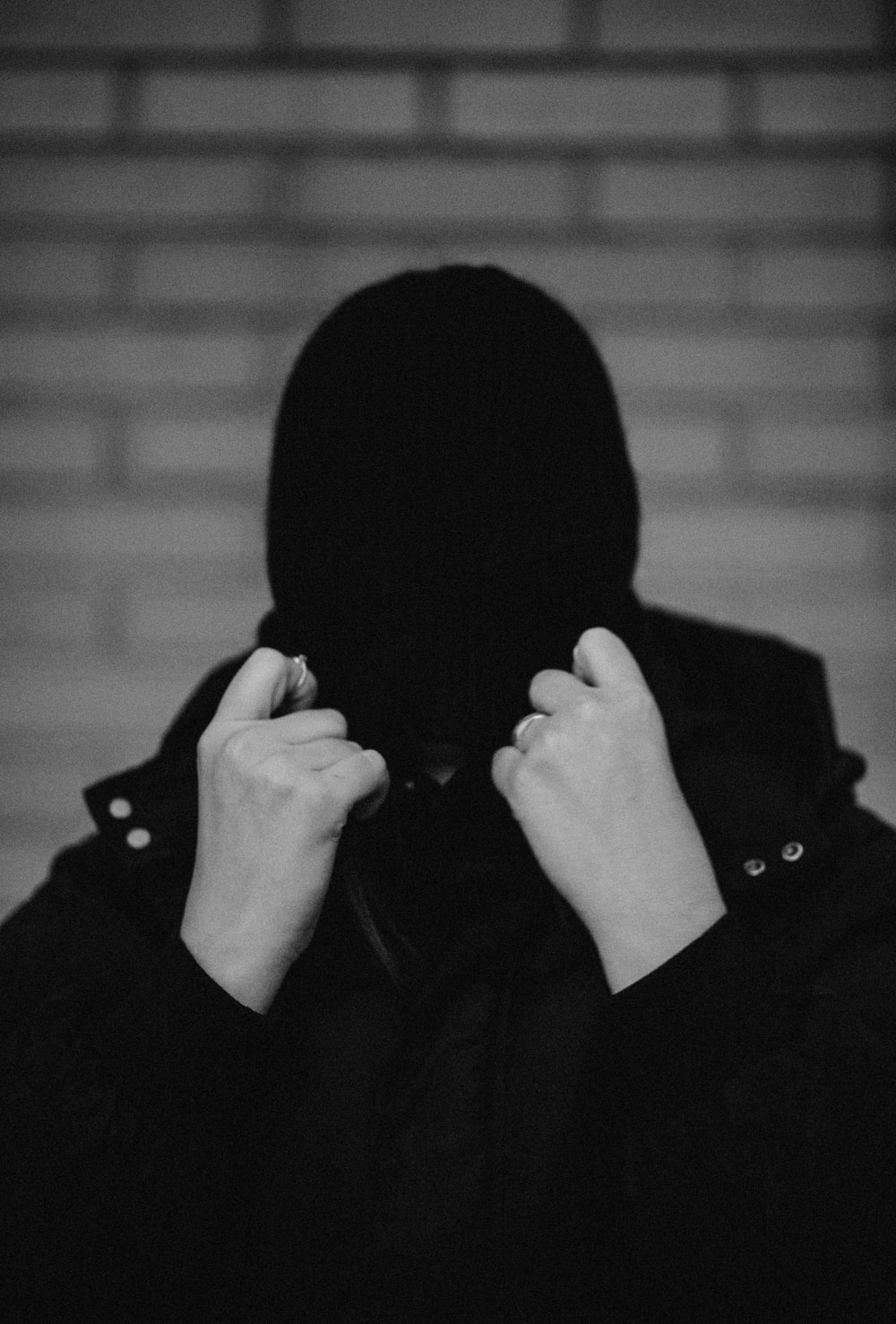 grayscale photo of person covering face with knit cap