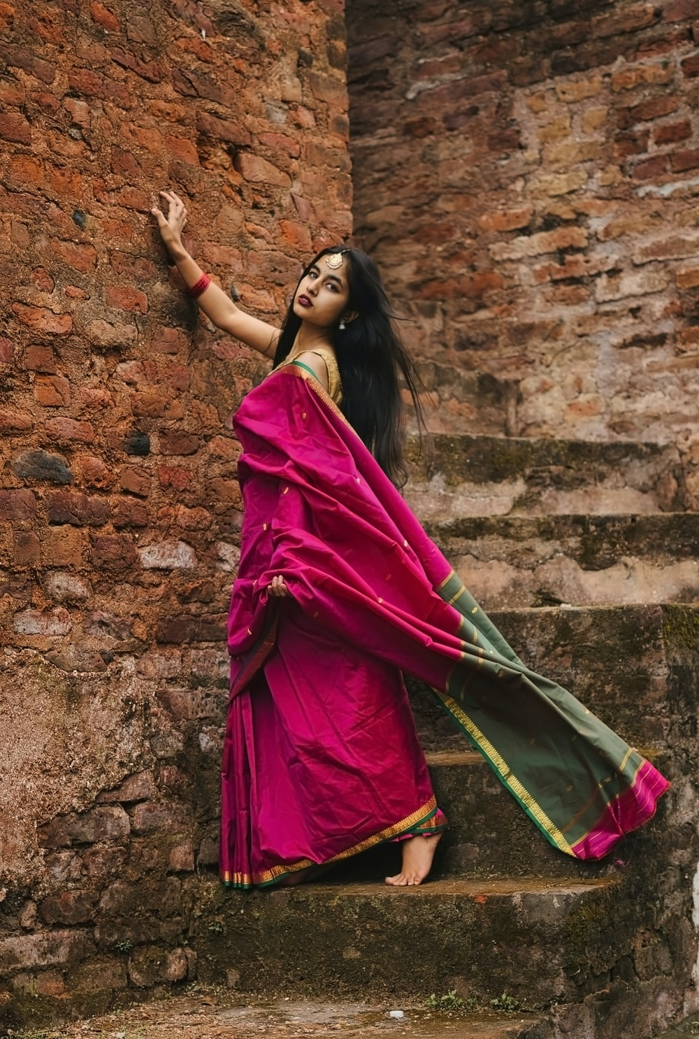 woman in red and purple sari dress leaning on brown brick wall