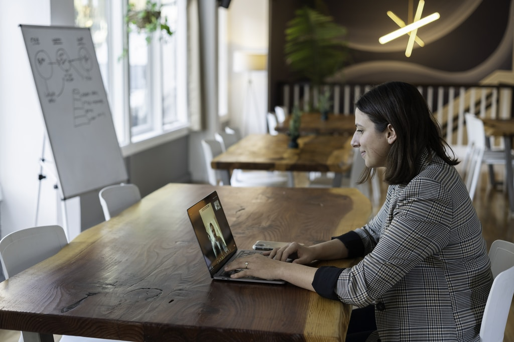 woman in gray and white striped long sleeve shirt using silver macbook