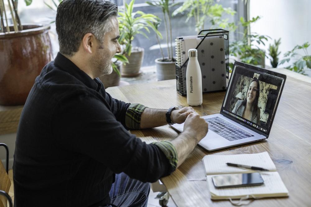 man in black sweater using macbook pro