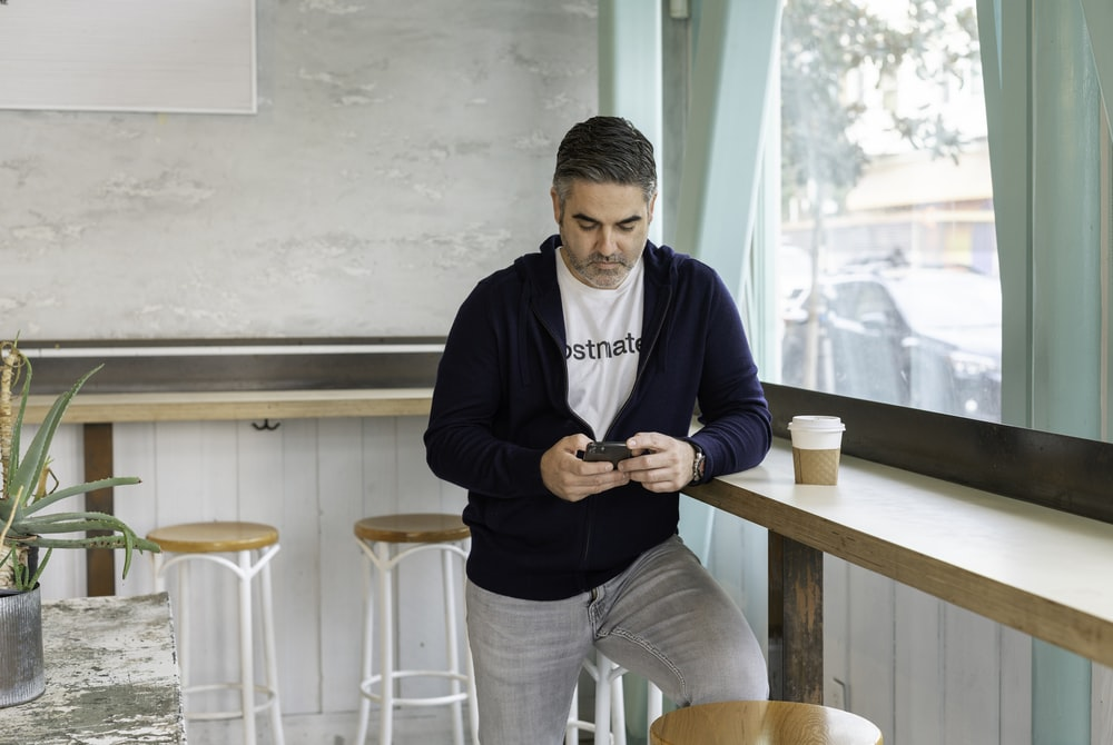 man in blue long sleeve shirt and gray pants holding black smartphone