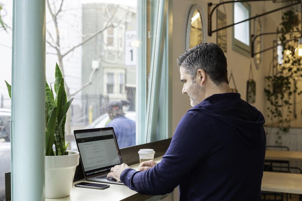 man in blue long sleeve shirt using macbook pro