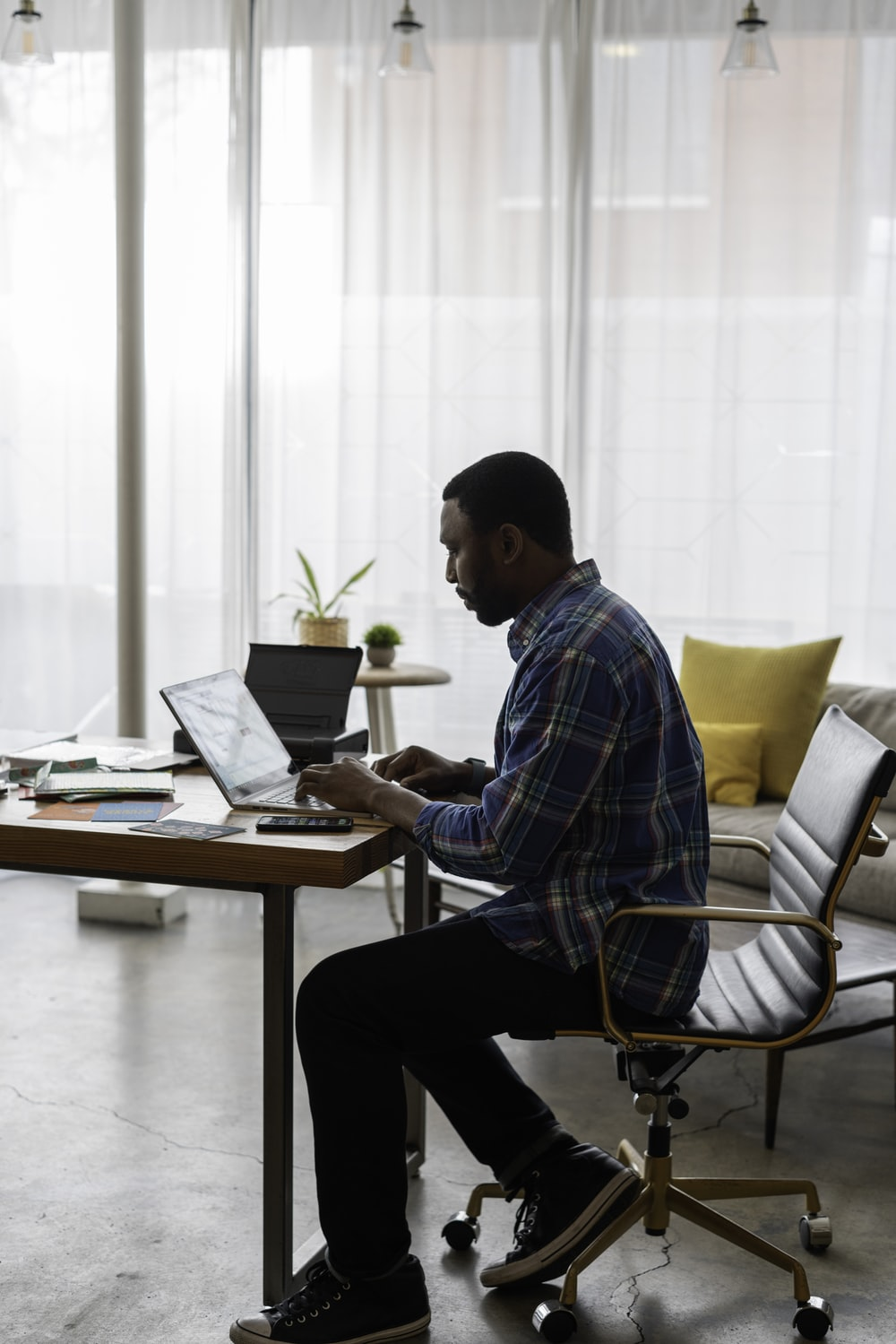 man in blue and white plaid dress shirt sitting on chair using laptop computer
