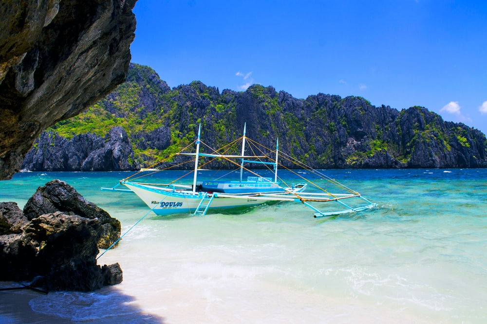 blue and white boat on seashore during daytime