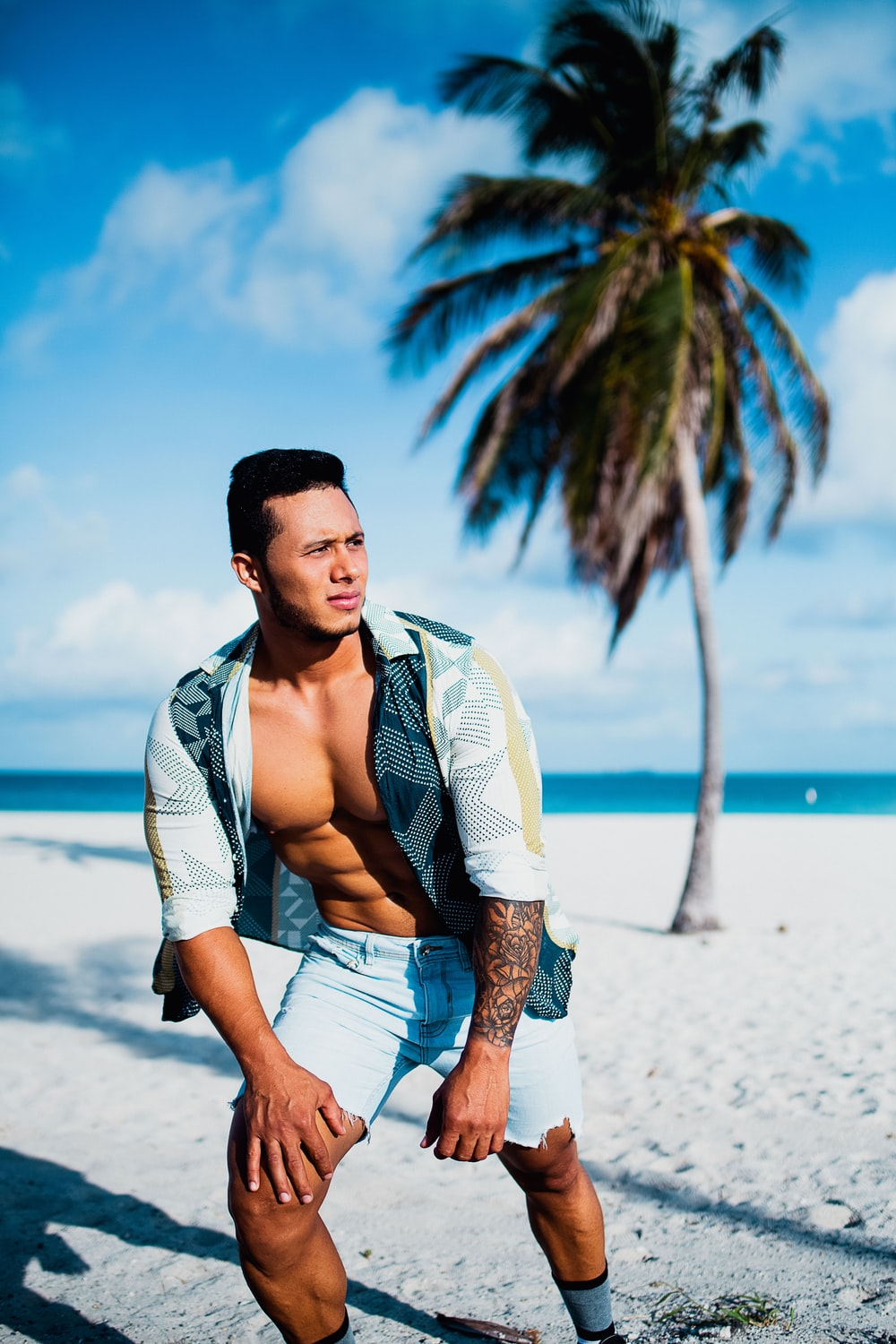 man in white button up shirt and blue denim shorts standing on beach during daytime
