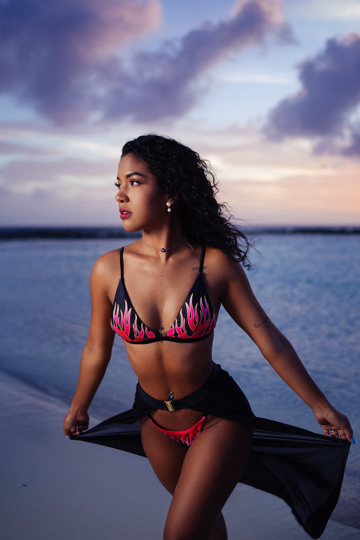 woman in red bikini sitting on black boat on sea during daytime
