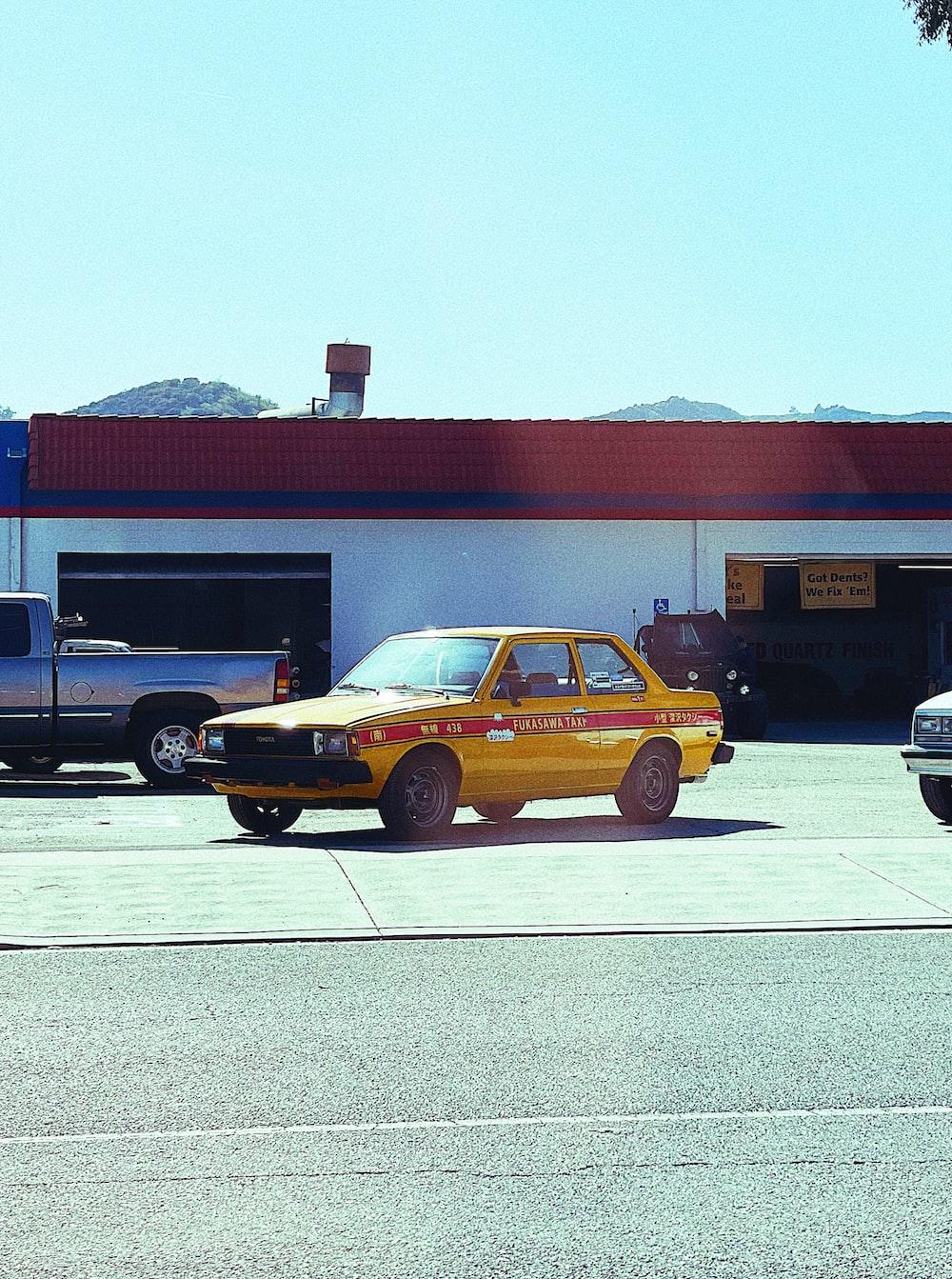 yellow sedan parked near brown building during daytime