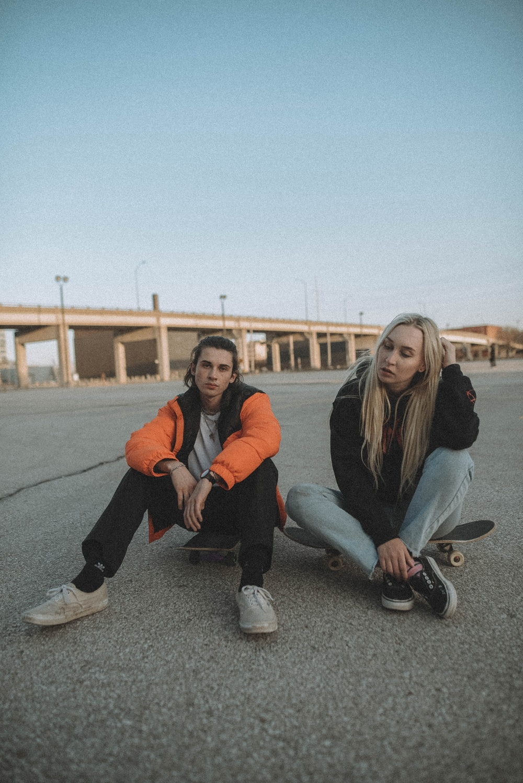 3 women sitting on gray concrete floor during daytime