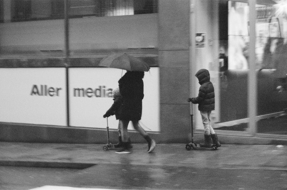 grayscale photo of 2 women walking on hallway