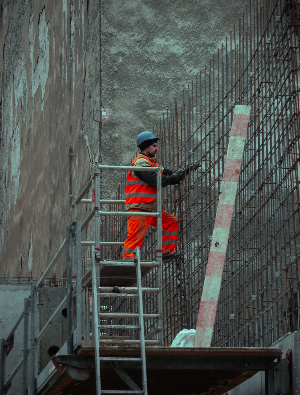 man in red jacket and blue cap standing on ladder