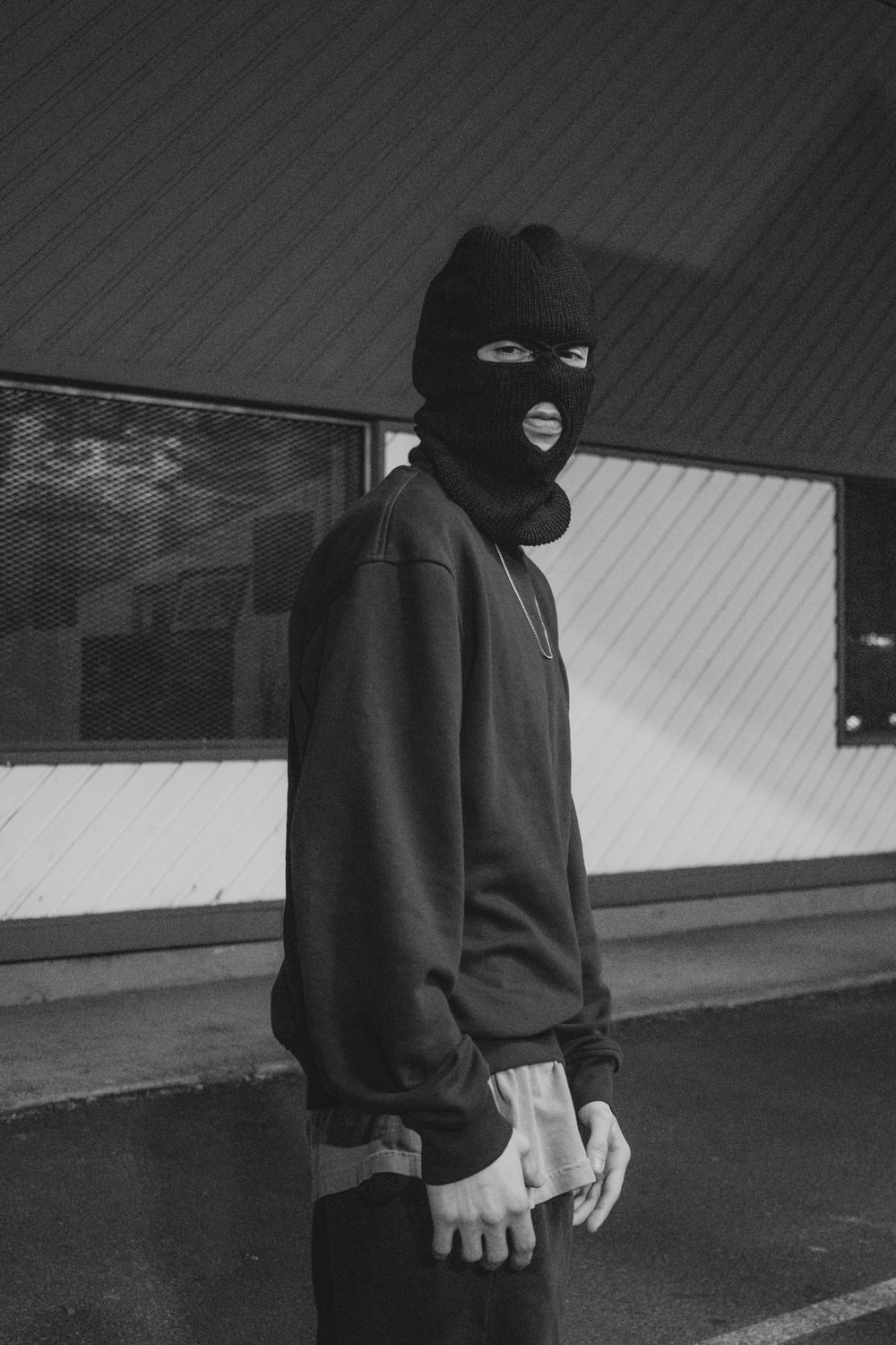 person in black mask and gray coat