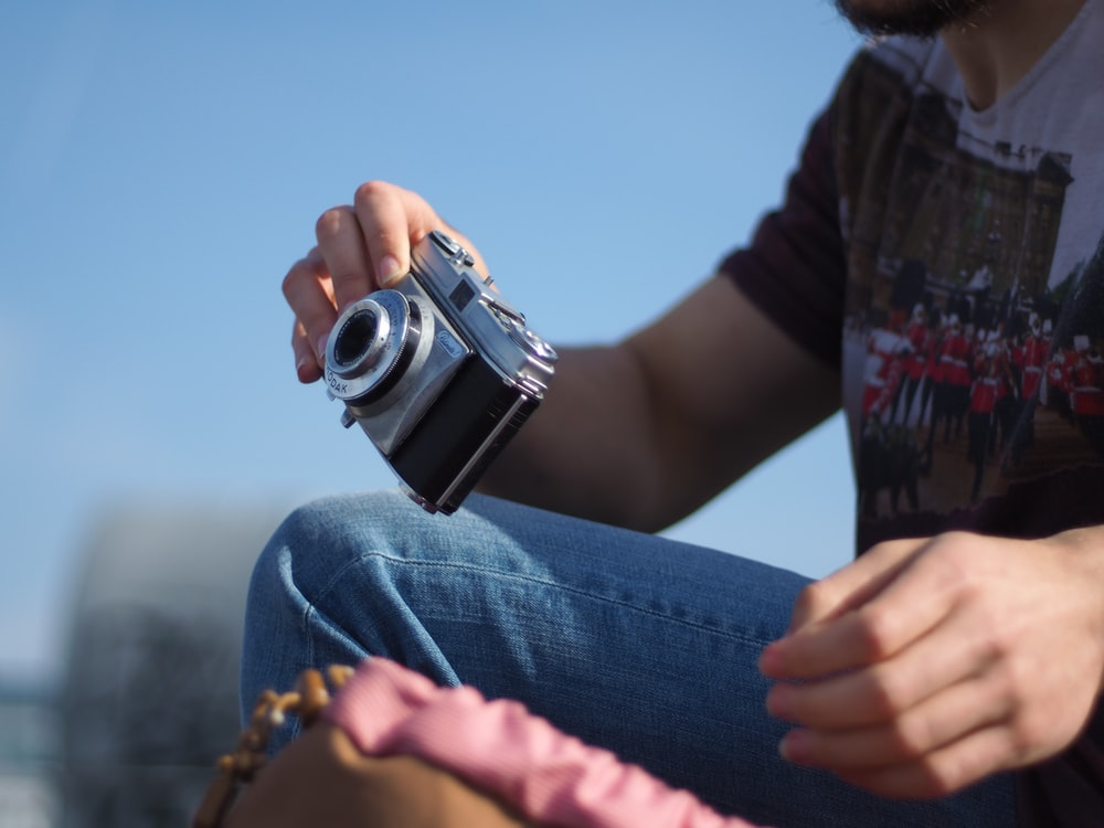 person in blue denim jeans holding black and silver dslr camera