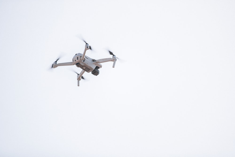 white and brown drone in mid air