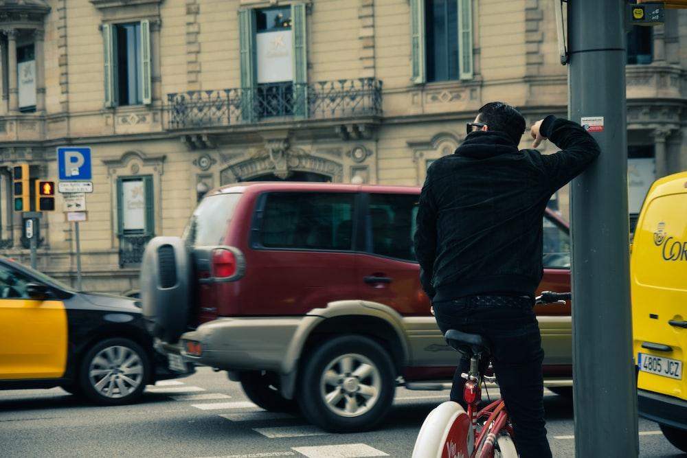 man in black jacket riding red bicycle during daytime