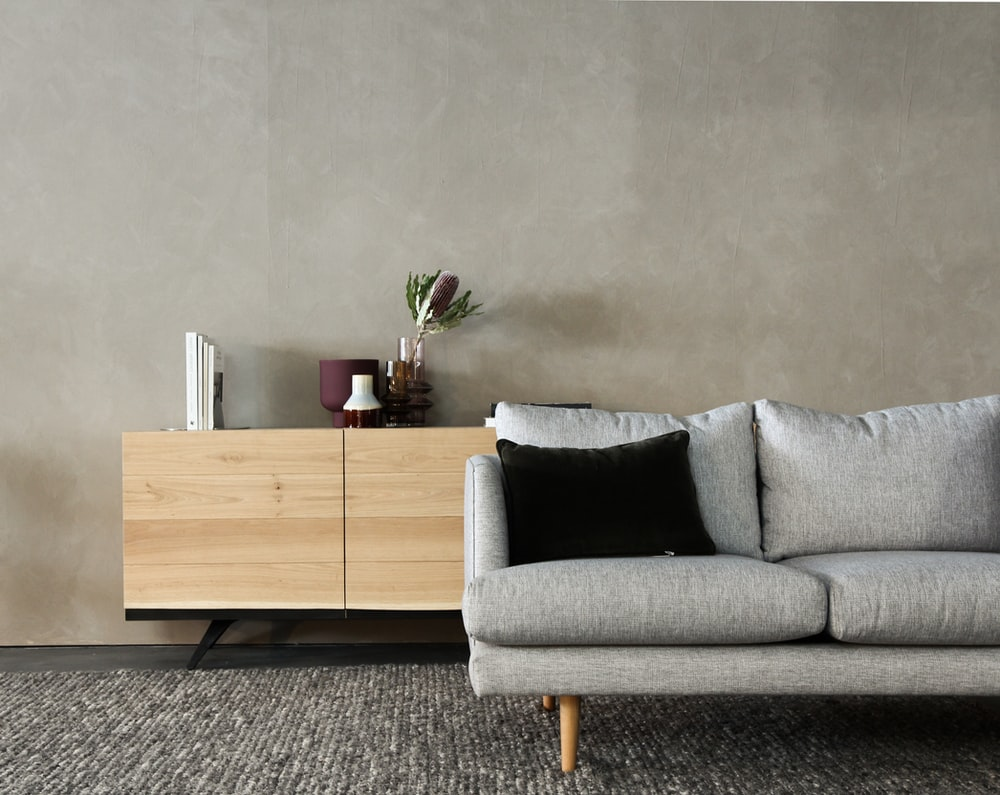 gray cushion couch beside brown wooden cabinet