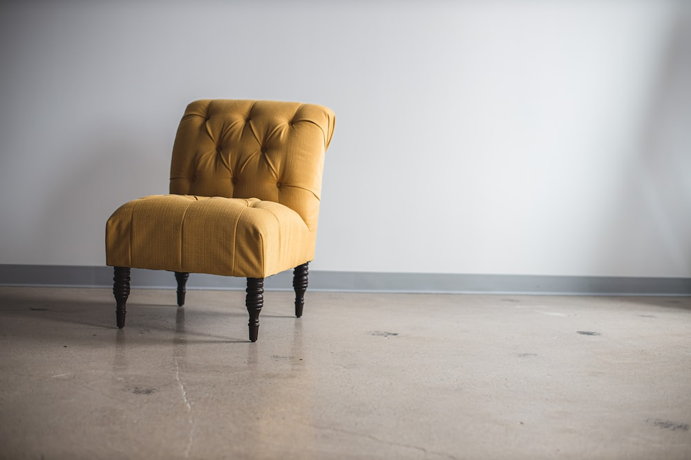 person in black pants standing beside white leather armchair