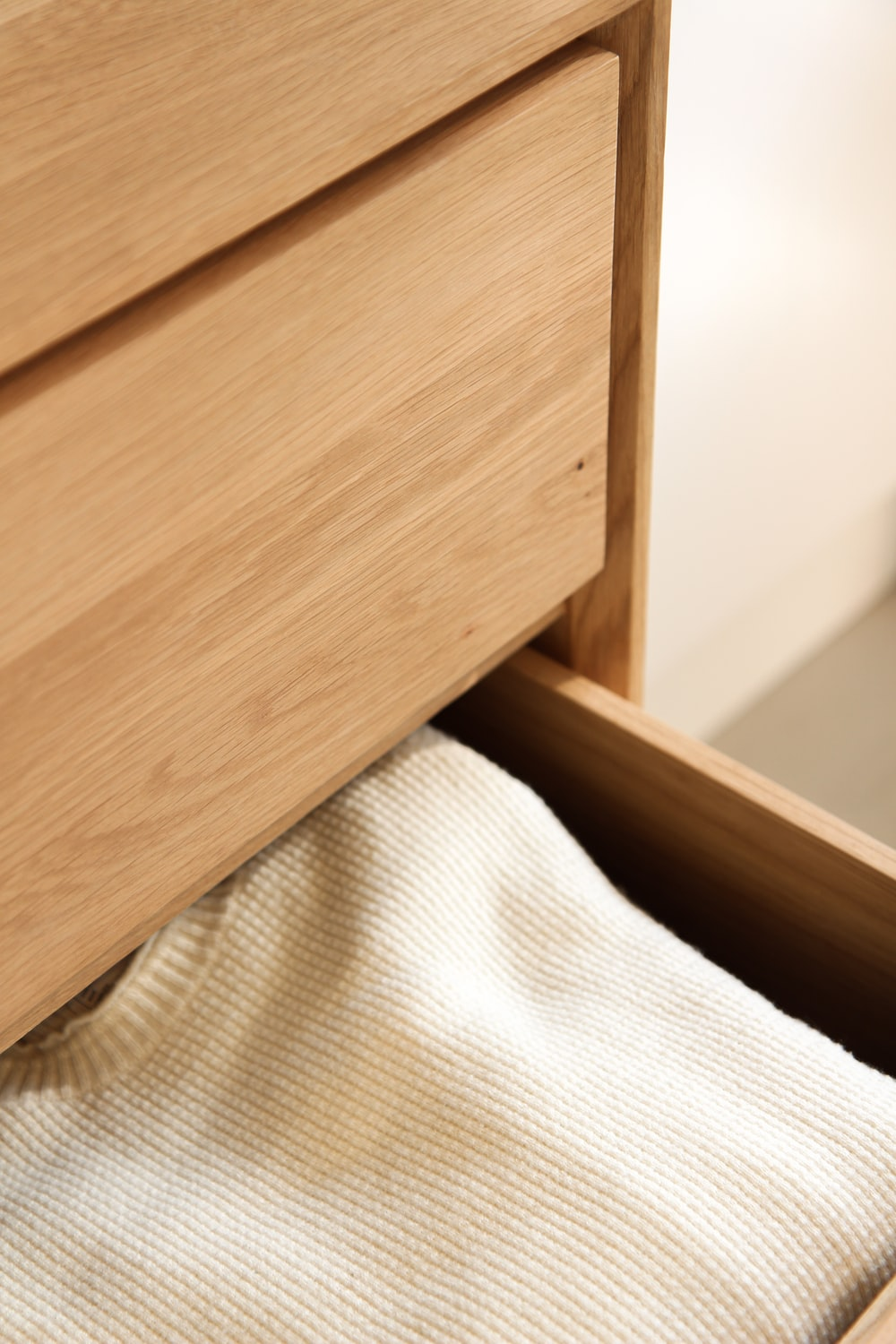 white textile beside brown wooden drawer