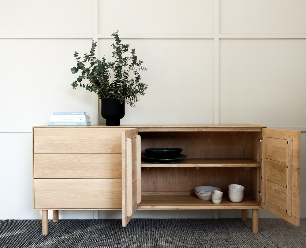 brown wooden cabinet beside green potted plant