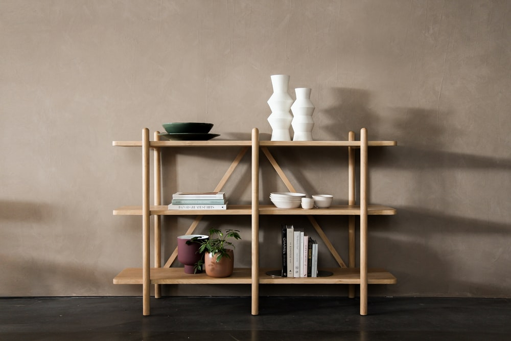 brown wooden 3 layer shelf with white pillar candles