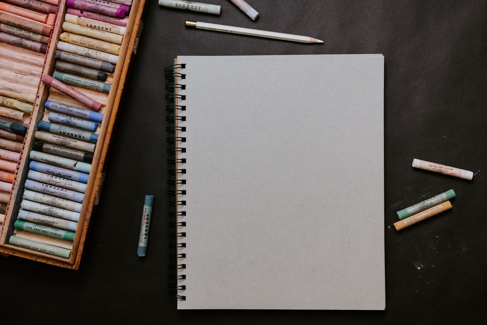 white spiral notebook beside white pen