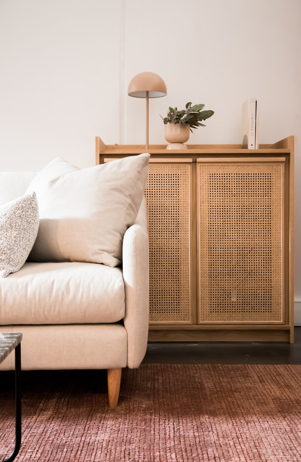 brown wooden cabinet beside white throw pillow