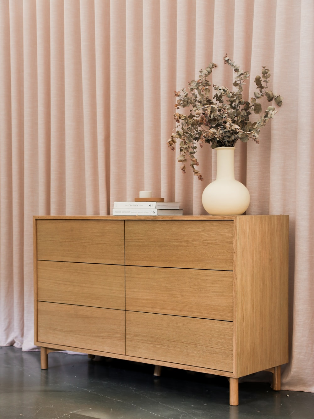 brown wooden cabinet beside white ceramic vase with flowers