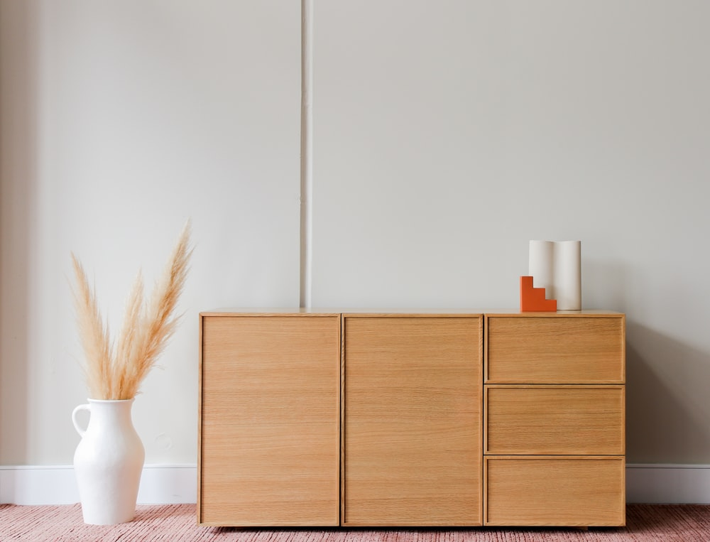 brown wooden cabinet beside white wall