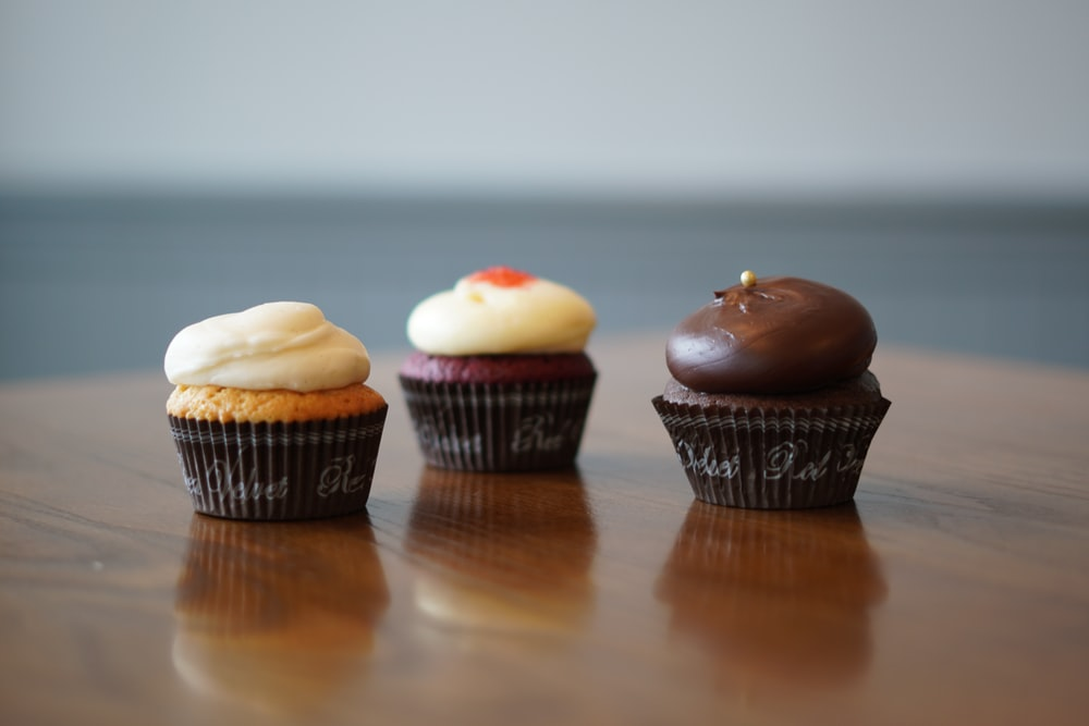 three cupcakes on brown wooden table