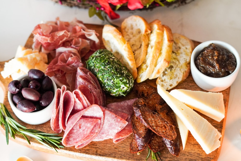 sliced meat with vegetable and bread on brown wooden chopping board
