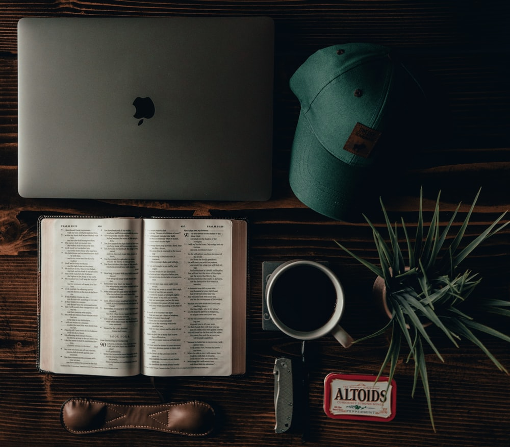 open book beside black and red digital watch and silver macbook
