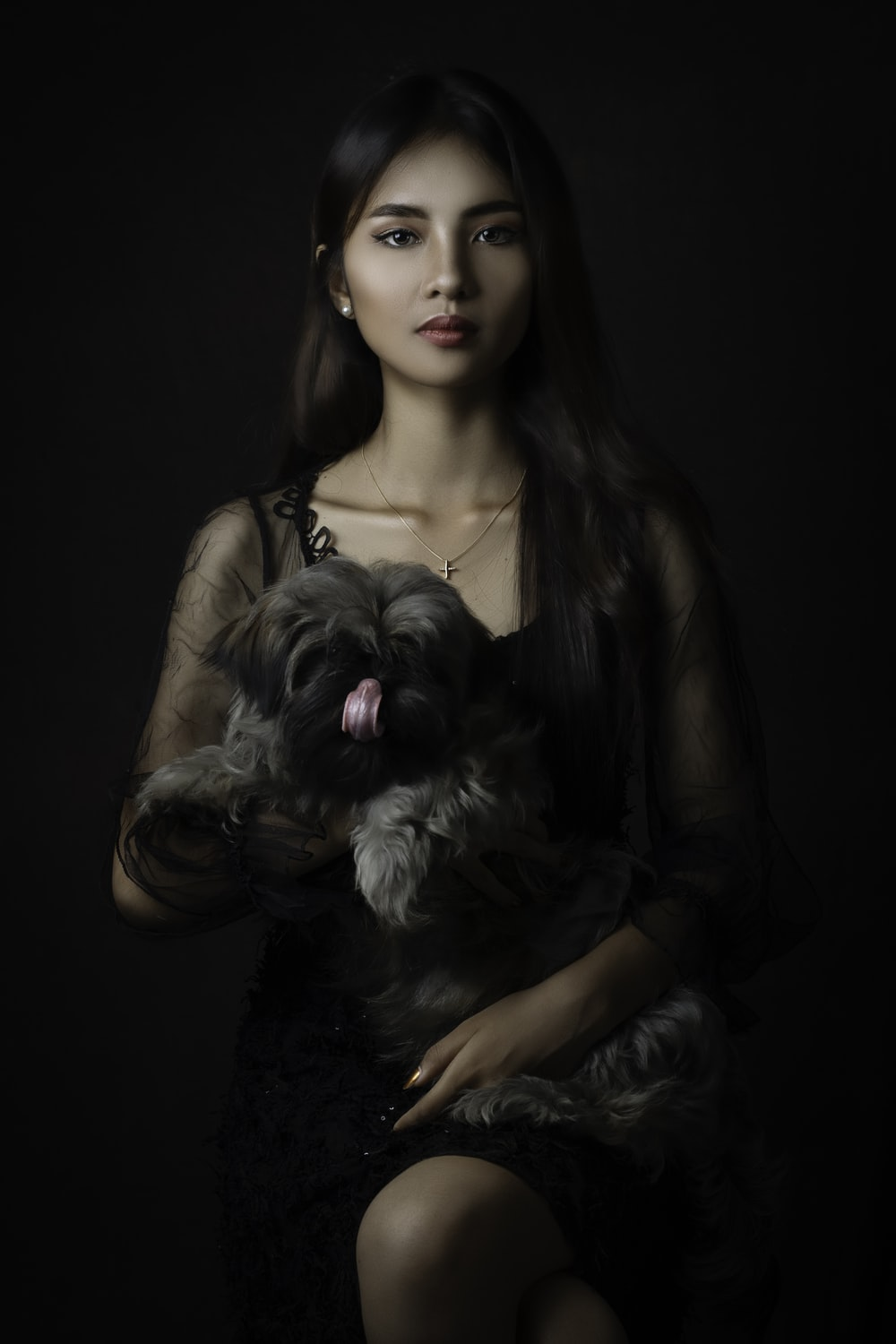 woman in brown sleeveless top holding black and white long coated small dog