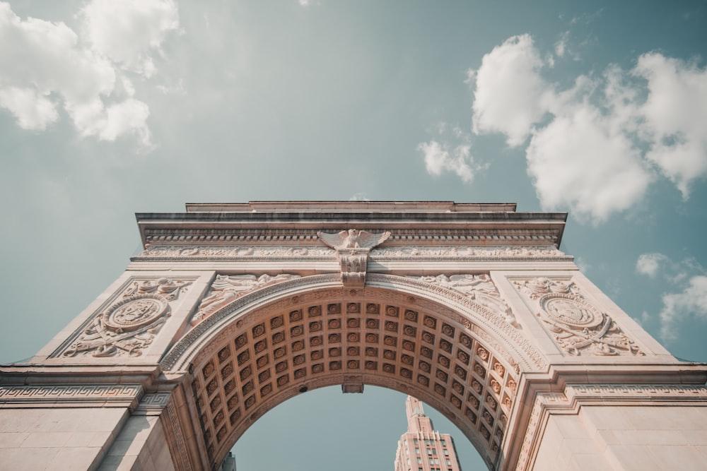 arc de triomphe under white clouds during daytime