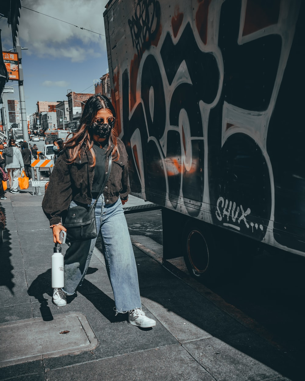 woman in black jacket and blue denim jeans walking on pedestrian lane during daytime