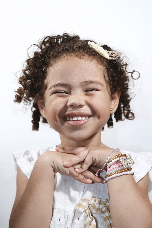 girl in white sleeveless shirt smiling
