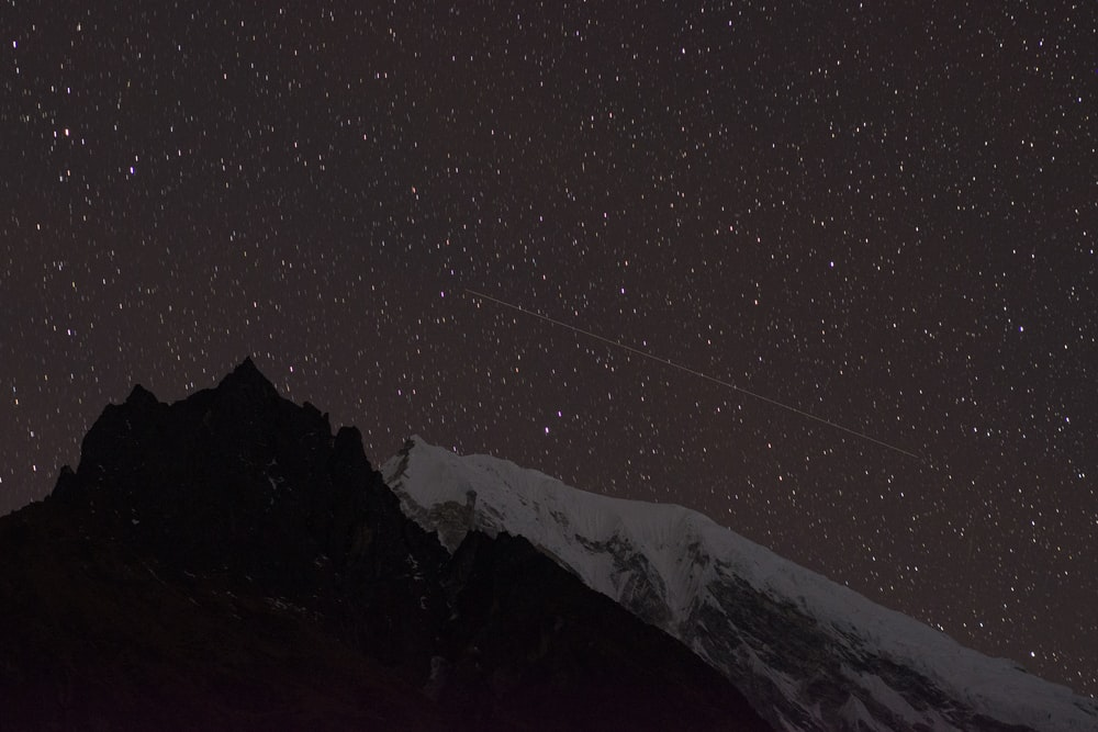 snow covered mountain under clear sky during night time