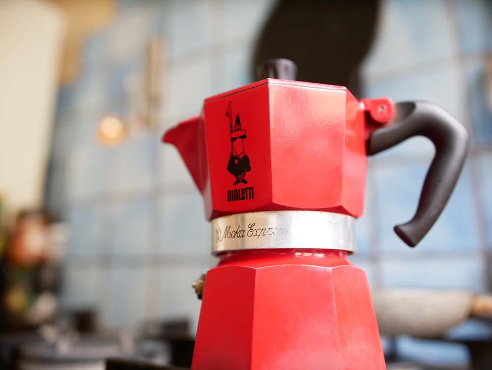 red coffee maker on brown wooden table