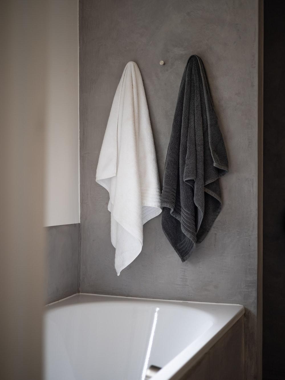 white bath towel on white ceramic bathtub